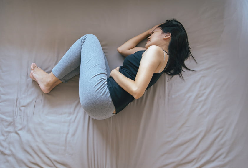 Asian female having painful stomachache,Woman suffering from abdominal pain,Period cramps