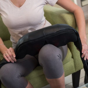 Woman applying the Solio T-Massager on her front left tight