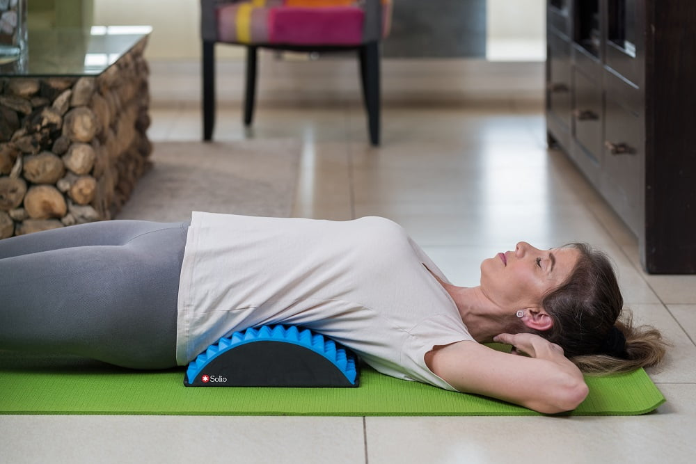 Woman using the Solio Back Stretcher